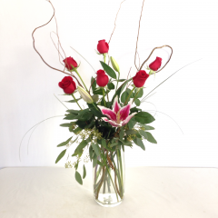 "A stunningly elegant arrangement of stargazer lilies and red roses in a tall vase.  Approx. 36""H x 12""W"