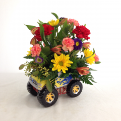 Go 'off road' with this bright arrangement in a monster truck novelty container.