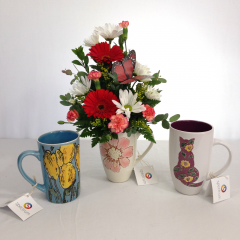 "A cute mixed floral arrangement in a decorative mug.  Colors of arrangement will go with the colors of the mug.  Call the shop with specific requests, or enter them in the special instructions.  Approx. 14""H x 8""W"