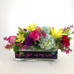 "A vibrant color arrangement of hydrangea, roses, gerberas, carnations, hypericum, and lilies with fillers.  Includes a chalkboard ribbon!  Approx. 9""H x 15""W"