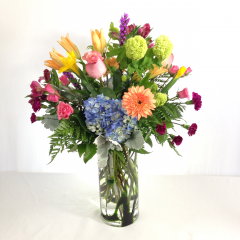 "A bold, beautiful mix of colors and flowers in a tall decorative cylinder vase.  Approx. 28""H x 20""W"