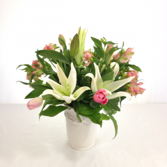 """White oriental lilies, alstroemeria (Peruvian lilies) and tulips in a white ceramic vase.  Approx. 17""""H x 14""""W"""