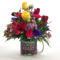 """A bright mix of flowers in a teacher's themed mug.  Approx. 11""""H x 8""""W"""