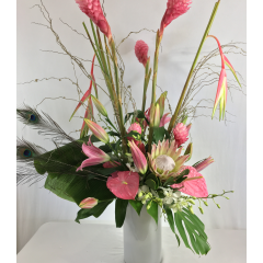 This primarily pink tropical arrangement features the stunning king protea, heliconia, ginger, anthurium, lilies and orchids has a touch of ostrich feathers and some lights intertwined to highlight these gorgeous flowers.