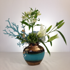 """A nautical inspired arrangement of white lilies, blue hydrangea, alstroemeria, and faux coral in a copper/blue vase.  Approx. 22""""H x 22""""W"""