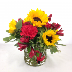 """A summery arrangement of sunflowers, alstroemeria, and carnations with a ladybug and moss wire wrapped vase.  Approx. 12""""H x 12""""W"""
