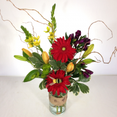 "Gerberas, alstroemeria, dubia, lilies, and bee decor celebrate the warmth of summer.  Approx. 24""H x 13""W"