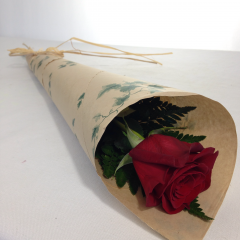 A single rose in brown paper with a bit of greenery and a raffia bow.  Filler available if requested. (Available for pick-up for much less!  $25 is our minimum for delivery.)
