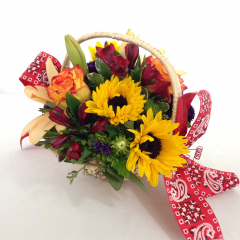"Nothing beats a picnic!  Lilies, roses, sunflowers, and alstroemeria with some asters.  Approx. 10""H x 10""W"