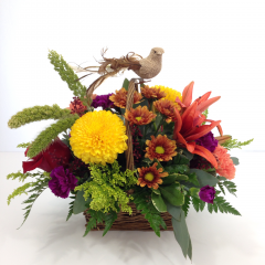 "A fall colored arrangement with a burlap bird.  Approx. 12""H x 14""W"