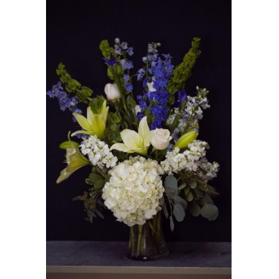 Ninth Street Flowers Durham - A lush and elaborate display of soft whites, deep blues and green, Winter Frost is a stunning arrangement containing white roses, white hydrangea, white lilies, blue delphinium and bells of Ireland. Seasonal foliage adds a finishing touch of texture.