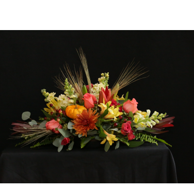 Ninth Street Flowers Durham - A long, elegant arrangement featuring roses, lilies, mums, stocks, leucadendrons (Safari Sunset) and snapdragons, accented with a pumpkin & wheat stalks. Ideal for a long, rectangular or harvest table  Please note, the flowers in your arrangement may vary from those seen in the image. We will make substitutions based on the freshest flowers available, keeping the spirit of the arrangement shown.  Enhance the arrangement's holiday elegance by adding a taper candle or two for $4 each.  Order by noon on Tuesday, November 26 to ensure Thanksgiving availability.