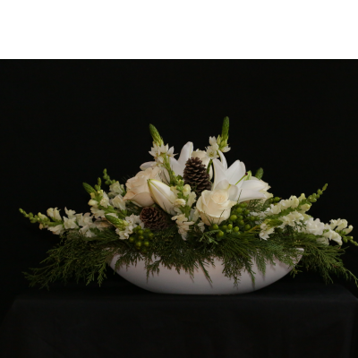 Ninth Street Flowers Durham - A wide, low, all white arrangement, featuring roses, lilies, snapdragons, Star of Bethlehem & fall greenery, accented with natural pine cones. Please note the actual flowers may vary from those shown in the photo, but the white color scheme and the spirit of the arrangement will be unchanged.  Add one or more tapers for added holiday appeal, for $4 each.
