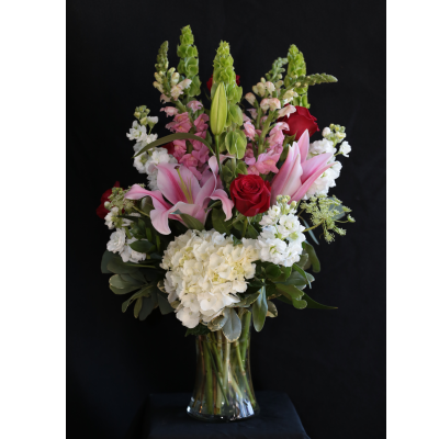 Ninth Street Flowers Durham - An enticing and sensual mix of fragrant lilies, roses, stock, and other seasonal favorites, makes this one of our best selling choices. PLEASE NOTE: Vase may vary from the one shown in the photo.