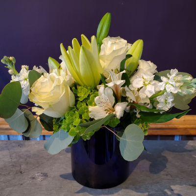 Ninth Street Flowers Durham - Created from a mix of white blossoms, this arrangement features roses, lilies, stocks & Peruvian lilies. We've placed it in a blue glass vase, but it could also be in a clear vase.