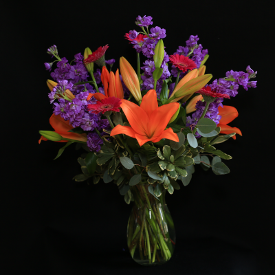 Ninth Street Flowers Durham - A dramatic display of hot summer colors, featuring orange lilies, hot pink Gerber daisies and purple stock.