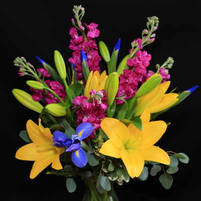 Ninth Street Flowers Durham - A European-style compact arrangement featuring bright yellow lilies, irises and stock.