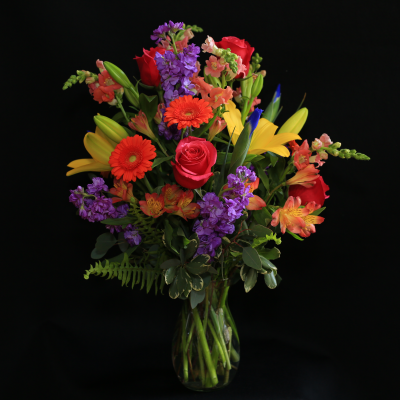 Ninth Street Flowers Durham - This arrangement features a spectacular rainbow of summer flowers, with roses, Gerber daisies, lilies, stock, snapdragons and Peruvian lilies.