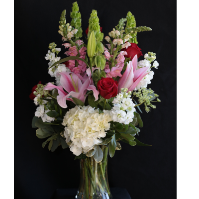Ninth Street Flowers Durham - An enticing and sensual mix of fragrant lilies, roses, stock, and other seasonal favorites, makes this one of our best selling choices. As pictured this is our average size arrangement.