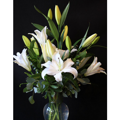 Ninth Street Flowers Durham - Fragrant white Oriental lilies are the essence of grace and peace. Convey the depth of your sentiments with our deluxe, tasteful arrangement of white Oriental lilies accented by lush greenery and curly willow in a clear glass vase.
