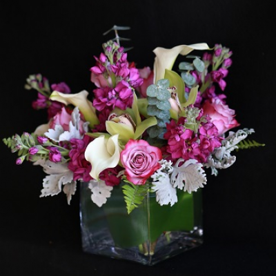 Ninth Street Flowers Durham - This chic arrangement in shades of magenta and lavender includes stock and roses, plus white mini callas, is displayed in a clear glass cube in our European Garden style. Exact flowers may vary due to seasonal availability.