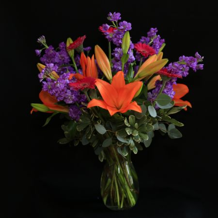 Ninth Street Flowers Durham - A dramatic display of brilliant, rich autumn colors, featuring orange lilies, hot pink Gerber daisies and purple stock.